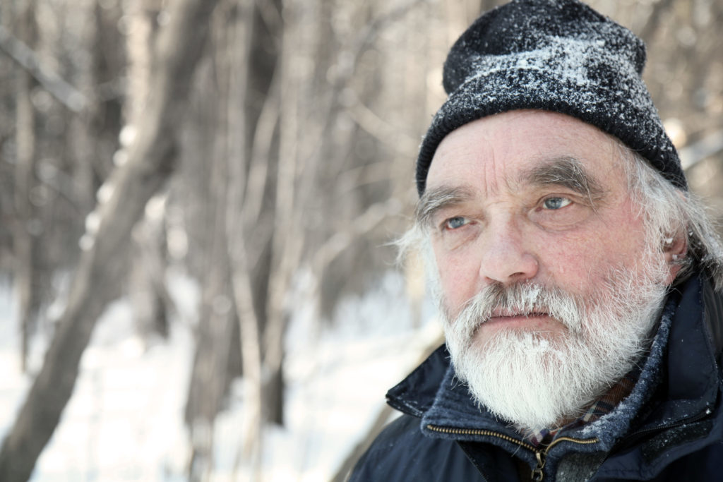 portrait of a senior adult with gray beard in winter forest